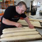 Spelt baker James Musk scores baguettes before baking. Photo by Gerard O'Brien.