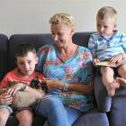 Stacey Jefferies, who had a mastectomy a year ago, with sons Cole, holding Coco the cat, and...