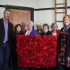 Standing with the commemorative display of 288 knitted poppies are (from left) Waitaki Mayor Gary...