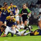 Stormers player Peter Grant is tackled by Jimmy Cowan and Mathew Berquist in the Super 14 rugby...