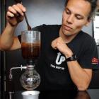 Strictly Coffee barista Logan Mamanu prepares a siphon brew. Photo by Gregor Richardson.