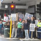 Student protesters, accompanied by a police officer, prepare to cross Moray Pl, Dunedin, during a...