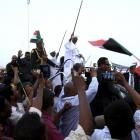 Sudanese President Omar al-Bashir (centre) waves to his supporters at the airport in the capital...