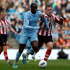 Sunderland's Craig Gardner (R) challenges Manchester City's Yaya Toure during their English...