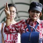 Supporters of an anti Thailand coup protester, Sombat Boonngamanong, flash the three-finger sign...