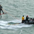 Surfing guru Titus Kinimaka has some fun on a hydrofoil surfboard towed behind a jet ski off Long...