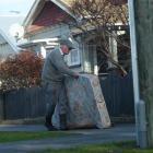 Surrey St resident Stuart Payne takes a damp mattress to a Dunedin City Council skip yesterday...