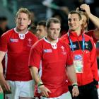 Suspended Wales captain Sam Warburton (R) walks on the field with his teammates after their Rugby...
