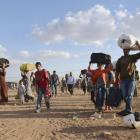 Syrian Kurds walk with their belongings after crossing into Turkey at the Turkish-Syrian border,...