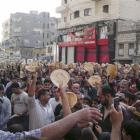 Syrian men carry bread loaves during a protest against Syrian President Bashar Assad's regime, in...