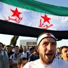 Syrian protesters living in Jordan hold a Syrian opposition flag during a protest in Amman...