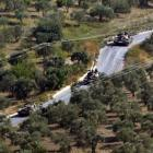 Syrian tanks, seen from the Turkish village of Saribuk, drive towards the town of Darkush in...