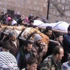 Syrians carry the bodies of members of the Free Syrian Army who were killed by the government's...