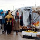Syrians refugees walk near street vendors after heavy rain, at the Al-Zaatari refugee camp in the...