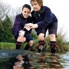Tahuna Intermediate pupils Thomas Woods (left) and Damin McCabe (both 12) take water samples from...