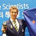 Taieri College pupil Ben Mulholland poses proudly next to the New Zealand flag after he won the...