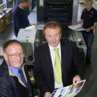 Taieri Print owner Peter Moore (left)  and  chief executive Ken Blair check a page from the new...