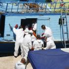 The body of a migrant is carried off a fishing boat, on which 19 migrants died last month.  The...