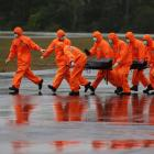 The body of an AirAsia QZ8501 passenger is carried to an ambulance from a Singapore Navy...