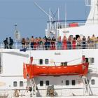 The crew of the Ukrainian MV Faina stand on the deck following a US Navy request to check on...