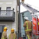 A member of the fire brigade examines the chimney at Eichardt's Private Hotel yesterday. Photo by...