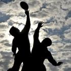 The sun rises behind a statue of rugby players reaching for the ball, outside Twickenham in west...