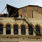 The top of the facade of the damaged building at 175 Rattray St is boarded up after the top...