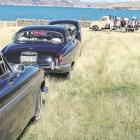 The wedding cars wait at the photo stop overlooking Lake Benmore while Joseph Cameron and...