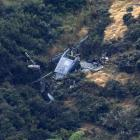 The wreckage of the Royal New Zealand Air Force Iroquois helicopter on the side of a hill in...