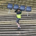 Thomas Smith (18), of Mosgiel, carries seats at the Carisbrook garage sale in Dunedin on Saturday.