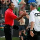 Tiger Woods celebrates with his caddie Joe LaCava after sinking his final putt on the 18th green...