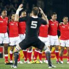 Tonga players watch as Ali Williams and his teammates perform the Haka before their Rugby World...