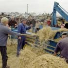 Tossing hay into a 1920s Booth Mac stationary baler is Ted Mills, with (from centre) Ronald Sheat...