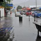 Traffic displaces water, making wake waves on flooded Gordon Rd on Saturday. Photos by Peter...
