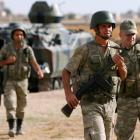 Turkish soldiers guard the Turkish-Syrian border near the Akcakale border crossing, southern...