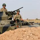 Turkish soldiers stand guard in an armoured personnel carrier on the Turkish-Syrian border near...