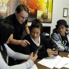 Tutor Timothy Ball (second from left) helps (from left) Faiumu Pavahi, Lisa Lam Cheung and...