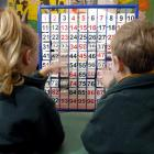 Two 5-year-old Dunedin pupils play with a number board at school. Photo by Gregor Richardson.