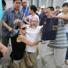 Two activists, centre, of an U.S. religious group are grabbed by security agents in Tiananmen...