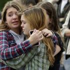 Two girls hug at Shoultes Gospel Hall church where families are reuniting after an active shooter...