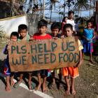 Typhoon victims hold a sign asking for food from motorists by the side of a road in Dolores,...