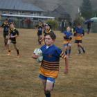 U11 Taieri's Hamish Faulks (11) sprints for the try line while being chased by Upper Clutha Black.