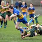 Lewis Kelly of Taieri with the ball is tackled by Mikaire Schooner of Eastern in the under 13...
