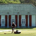 University Oval grounds manager Tom Tamati mows the pitch in front of the former art gallery, a...