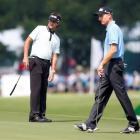 US golfer Bubba Watson (L) and his compatriot Jim Furyk watch Watson's putt on the seventh hole...