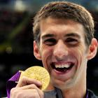 US swimmer Michael Phelps holds up the gold medal he won in the men's 100m butterfly. REUTERS...