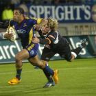 Otago winger Fetu'u Vainikolo is tackled by Sharks centre Francois Steyn during the Super 14...