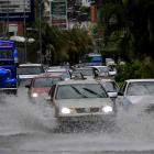 Vehicles drive through a street flooded by heavy rains caused by tropical storm Carlos, in...