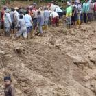 Villagers remove mud from the main road at Pasuruhan village in Wonosobo in this photo taken by...