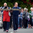 Vise MacKinlay (left) and Gerald Scanlan carry the cross from St Mary's Catholic Parish in...